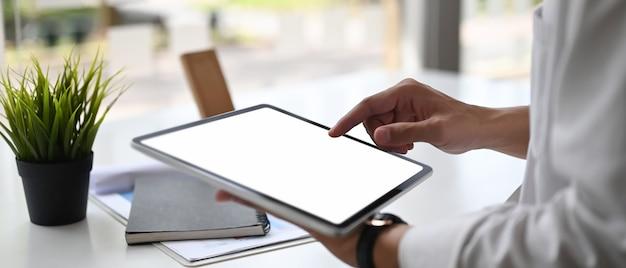 Крупным планом вид бизнесмена, работающего над планом своей компании при использовании цифрового планшета с пустым экраном в офисе.