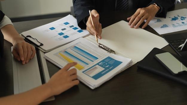 회의실에서 비즈니스 문서를 분석하는 기업인의 뷰를 닫습니다