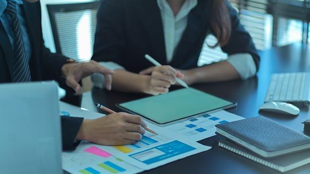 Крупным планом вид бизнесменов, работающих вместе с планшетом и документами в конференц-зале