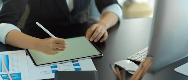 デジタルタブレットとオフィスのテーブルで書類を扱う実業家のクローズアップビュー