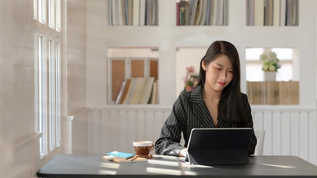 현대 직장에서 창 옆에 앉아 디지털 태블릿에 입력하는 경제인의보기를 닫습니다