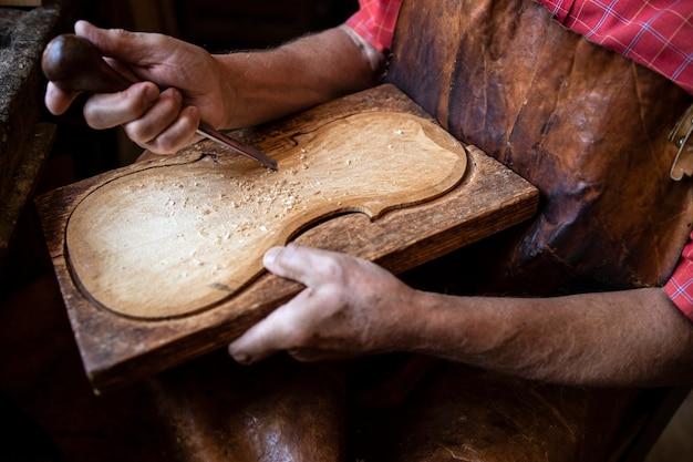 그의 구식 작업장에서 나무를 형성하고 조각하는 목수의 손보기를 닫습니다.