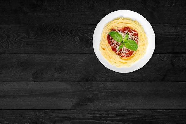 Крупным планом вид спагетти с сыром, изолированных на черном деревянном столе.
