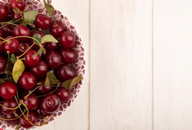 Крупным планом вид вишни с листьями в миске на деревянном фоне с копией пространства