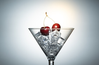 Close up view of cherry among ice in a martini glass in white background with flare .