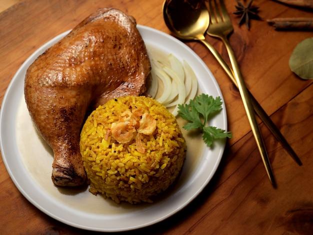 레스토랑의 나무 테이블에 향신료에 절인 쌀과 치킨 비리 야니의 뷰를 닫습니다