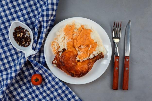 灰色の背景の白い皿にご飯とチキンカレーの脚のクローズアップ表示。青いナプキン、フォーク、ナイフ、コショウは、組成物を飾る。