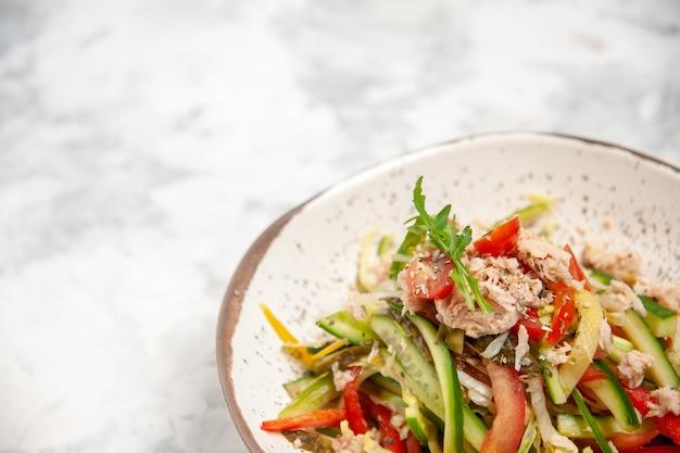 空きスペースのあるステンド グラスの白い表面に野菜とチキン サラダのクローズ アップ ビュー