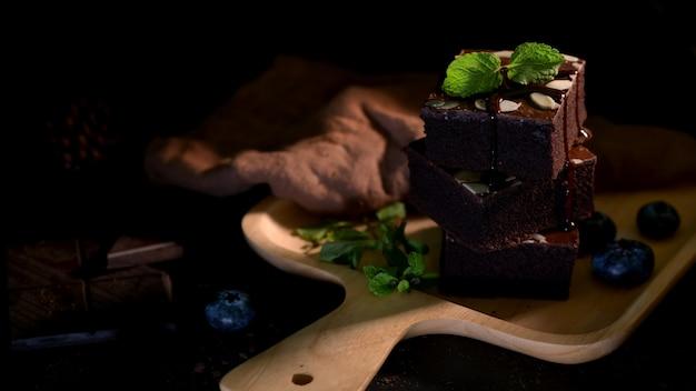 上にミントの葉を持つ木製トレイ上のチョコレートブラウニーのクローズアップ表示