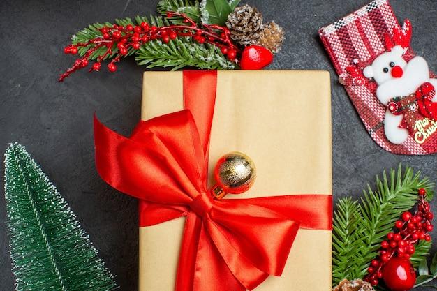 어두운 배경에 나비 모양의 리본과 전나무 가지 장식 액세서리 크리스마스 양말과 아름다운 선물로 크리스마스 분위기의 뷰를 닫습니다