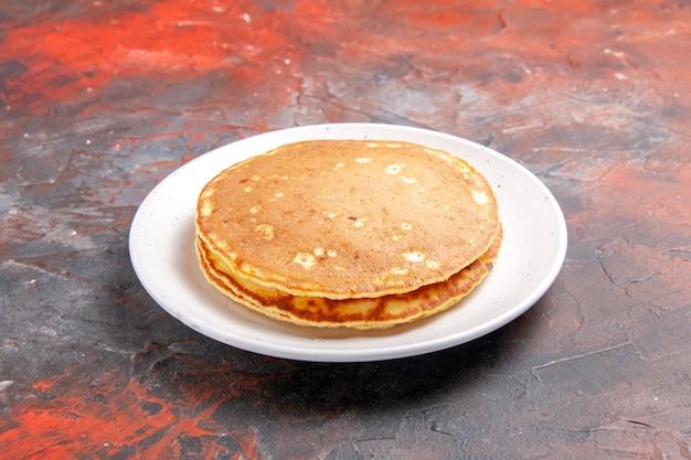 混合色の白いプレート上の古典的なアメリカのバターミルクパンケーキのクローズアップビュー