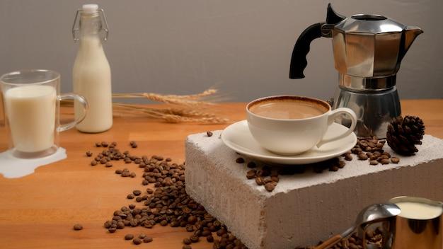 커피 컵, 커피 포트 및 커피 원두와 밀로 장식 된 우유와 함께 커피 테이블의보기를 닫습니다