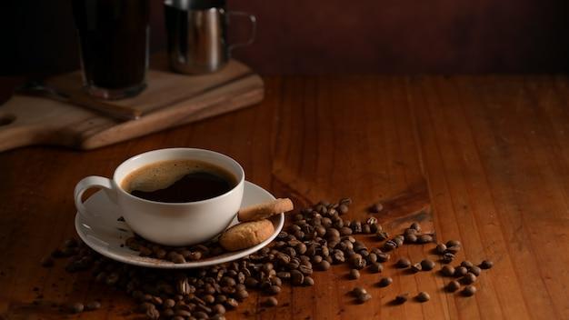 뜨거운 커피 컵과 커피 콩으로 장식 된 비스킷 커피 테이블의보기를 닫습니다