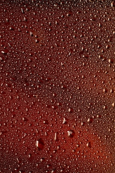 Крупным планом вид холодных капель на фоне стакана пива. текстура охлаждающего алкогольного напитка с макросами на стеклянной стене. шипение или всплытие на поверхность. темно-коричневого цвета.