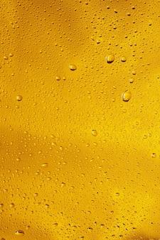 Крупным планом вид холодных капель на фоне стакана пива. текстура охлаждающего алкогольного напитка с макросами на стеклянной стене. шипение или всплытие на поверхность. золотистого цвета.