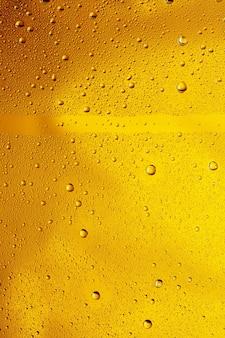 Крупным планом вид холодных капель на фоне стакана пива. текстура охлаждающего алкогольного напитка с макросами на стеклянной стене. шипит или всплывает на поверхность. золотистого цвета.