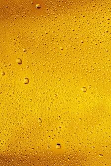 ビールの背景のガラスの冷たい滴のクローズアップビュー。ガラスの壁にマクロの泡が付いた冷却アルコール飲料のテクスチャ。表面の上部に浮き上がったり浮いたりします。黄金色。