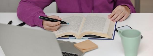 彼女のセミナーを準備するために本を読んで大学生のクローズアップ表示