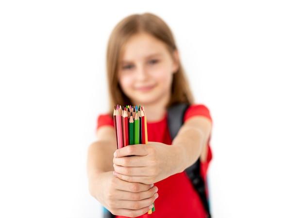 白の小さな女の子の手でカラフルな鉛筆のクローズアップ表示