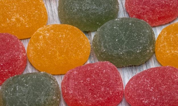 Закройте вверх по взгляду красочных вкусных конфет мармелада разбросанных на деревенское