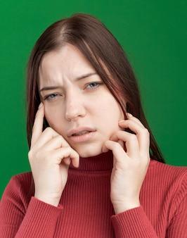 녹색 벽에 격리된 생각하는 몸짓을 하는 전면 만지는 얼굴을 바라보는 혼란스러운 젊은 예쁜 여성의 클로즈업 보기