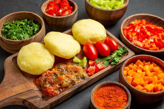黒いテーブルの上で新鮮な野菜とみじん切りの食品を使った料理のクローズアップビュー