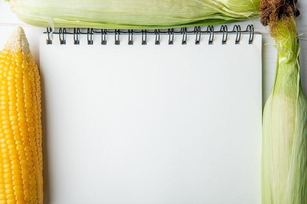 トウモロコシの穂軸とコピースペース付きメモ帳のクローズアップビュー1