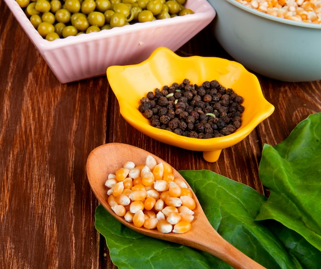 木製のテーブルに木のスプーンでトウモロコシの種子とほうれん草と黒胡椒のボウルのクローズアップビュー