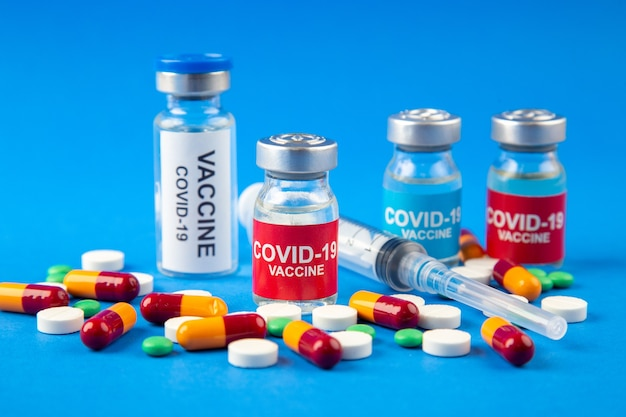 Крупным планом вид вакцины covid в медицинских ампулах, таблетках, капсулах, одноразовых шприцах на темно-мягком синем фоне