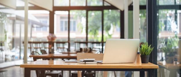 ノートパソコンと背景のぼやけたインテリアとカフェのコワーキングスペーステーブルのクローズアップビュー