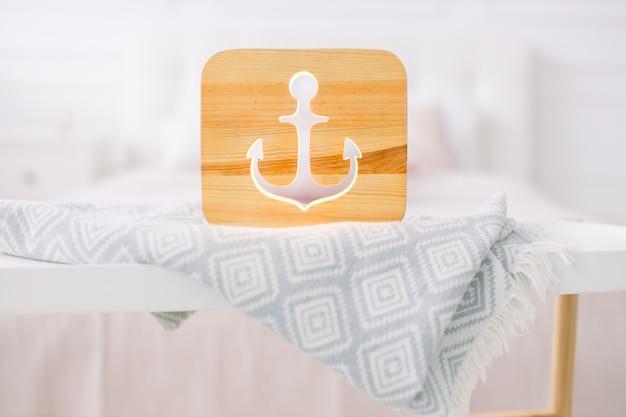 Крупным планом вид уютной деревянной ночной лампы с вырезанным якорем изображением на сером одеяле в уютном светлом интерьере спальни.