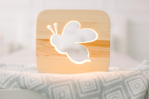 Крупным планом вид уютного деревянного ночника с вырезанным изображением пчелы или насекомого на сером одеяле в уютном светлом интерьере спальни