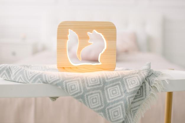 Крупным планом вид уютной деревянной ночной лампы с изображением лисы на сером одеяле в уютном светлом интерьере спальни.