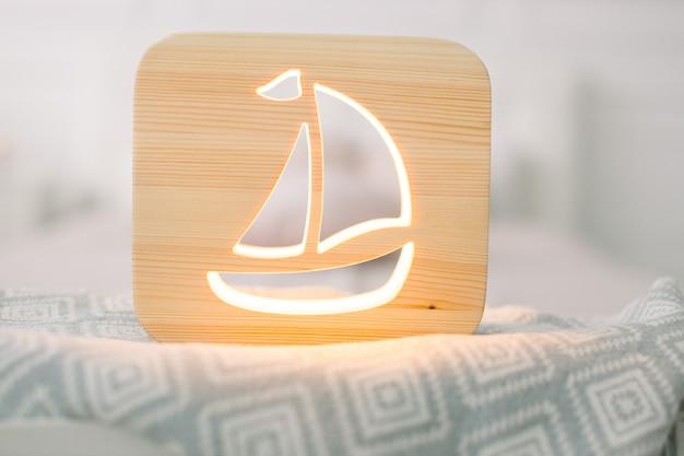 Крупным планом вид уютной деревянной ночной лампы с изображением корабля вырезать, на сером одеяле в интерьере уютной светлой спальни.