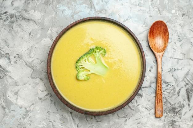 灰色のテーブルの上の茶色のボウルとスプーンでクリーミーなブロッコリースープのクローズアップビュー