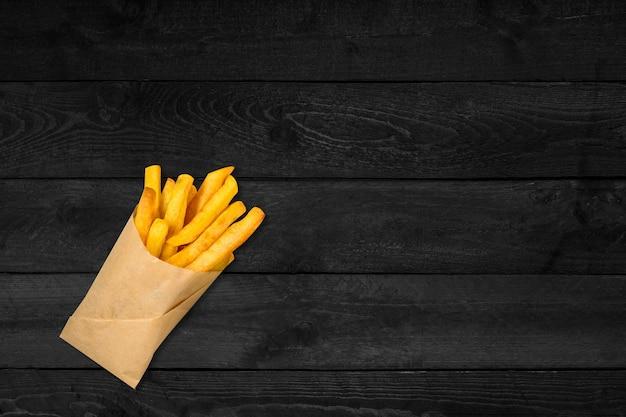 Крупным планом вид хрустящего картофеля, изолированного на черном деревянном столе.