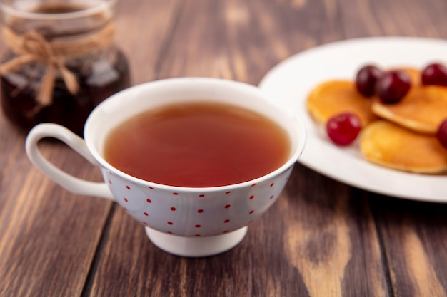 Крупным планом вид чашки чая с тарелкой блинов и банкой клубничного варенья на деревянном фоне