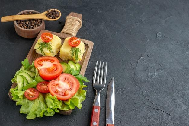 黒い表面に設定された木の板カトラリーにカットされた新鮮なトマトとキュウリのチーズのクローズ アップ ビュー