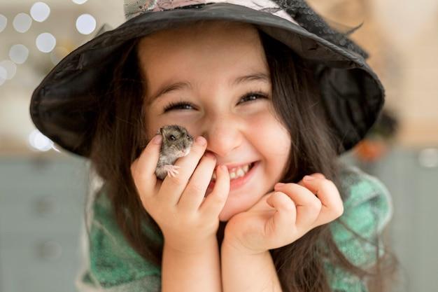 Крупным планом милая маленькая девочка держит хомяка