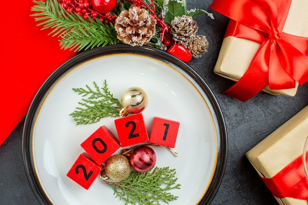 Крупным планом вид номеров аксессуаров украшения на тарелке и красивых подарков еловых веток хвойных шишек на темном столе