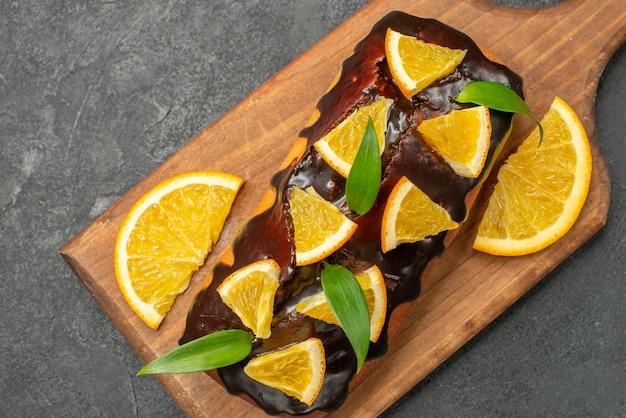 블랙 테이블에 커팅 보드에 오렌지와 초콜릿으로 장식 된 맛있는 케이크의 뷰를 닫습니다