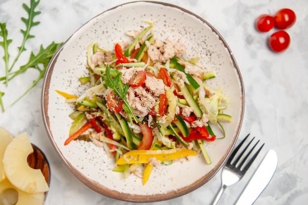 空きスペースのあるステンド グラスの白い表面に野菜トマト ドライ パイナップル カトラリー セットのおいしいチキン サラダのクローズ アップ ビュー