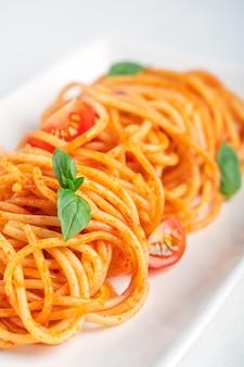 Крупным планом вид вкусных итальянских спагетти из макарон, приготовленных в красном соусе с листьями базилика