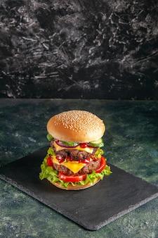 空きスペースのある黒い表面に濃い色のトレイにトマトグリーンを添えたおいしい肉サンドイッチの接写