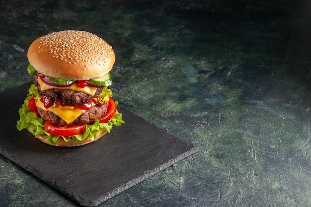 검은 색 표면의 오른쪽에 진한 색 트레이에 녹색 토마토와 함께 맛있는 고기 샌드위치의 뷰를 닫습니다