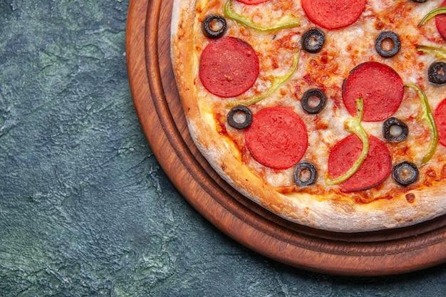 여유 공간이있는 진한 파란색 표면의 왼쪽에 나무 커팅 보드에 맛있는 피자보기를 닫습니다.