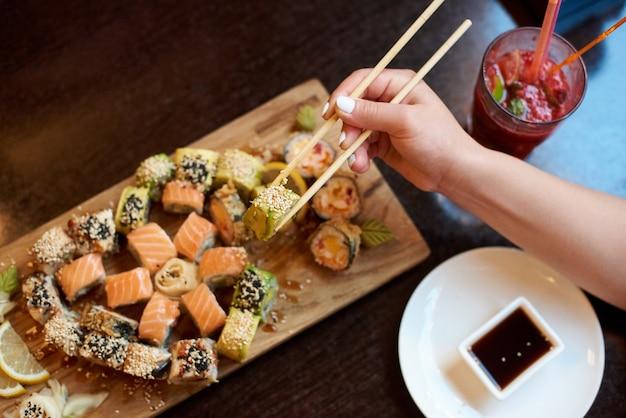 Крупным планом вид вкусных ролл-суши, поданных на деревянной доске с палочками для еды, соевым соусом и коктейлем