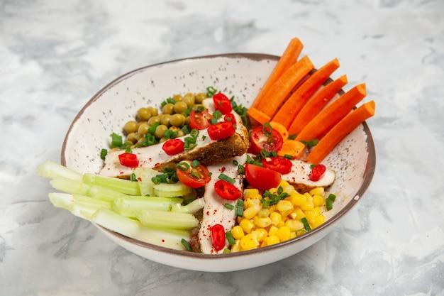 空きスペースのある白い表面のプレートにさまざまな食材を入れたおいしいサラダの接写