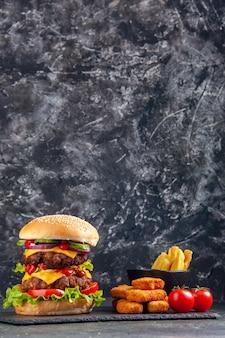 Крупным планом вид вкусного сэндвича на подносе темного цвета и куриных наггетсов на черной поверхности