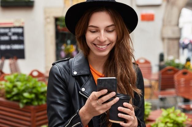 기쁘게 젊은 여자의 뷰를 닫습니다 휴대 전화 데이터 인터넷 연결을 사용하고 문자 메시지를 읽습니다.